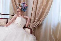 Bliss!. Lovely bride sitting on a hotel chesterfield and having a large flowers bun Royalty Free Stock Photography