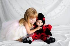 Blissfilled-Schwester-Hugs Her Younger-Schwester Dressed als Marienkäfer Lizenzfreie Stockfotos