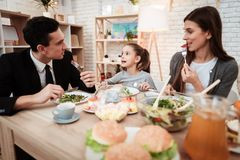 Blissful family eating dishes at table together. Parents with their daughter gathered at table. royalty free stock images