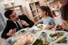 Blissful family eating dishes at table together. Parents with their daughter gathered at table. stock image