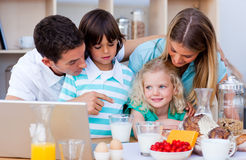 Blissful family using laptop during the breakfast Royalty Free Stock Photography