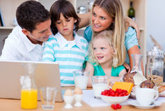 Blissful family using laptop during the breakfast Stock Image