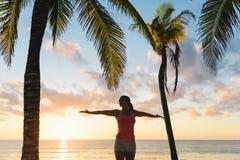 Blissful fitness woman enjoying beach sunset workout. Blissful fitness woman enjoying outdoor summer sunrise or sunset workout at the beach. Happy female athlete Royalty Free Stock Photo