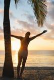 Blissful fitness woman enjoying beach sunset workout under palms Stock Images