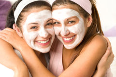 Blissful girls applying mask hugging each other. Blissful girls applying white facial mask hugging each other Stock Images