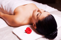 Blissful moments. Top view of beautiful young woman wrapped in towel lying on massage table and keeping eyes close Stock Image