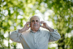 Blissful senior man listening to music Royalty Free Stock Photography