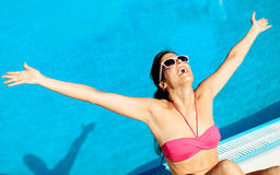 Blissful summer woman. Blissful woman having fun at swimming pool on summer vacation. Successful happy girl raising arms at poolside Royalty Free Stock Images