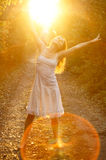 Blissful sunshine. Beautiful young girl dancing in the golden light of the setting sun on forest track Royalty Free Stock Images