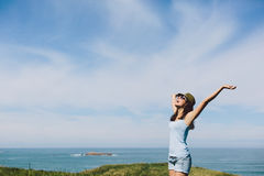 Blissful woman enjoying coast vacation travel. Blissful woman enjoying freedom raising arms to the sky towards the sea. Girl having fun and celebrating life  on Royalty Free Stock Image