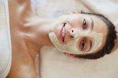 Blissful Woman Enjoying SPA. Top view closeup portrait of blissful young woman enjoying beauty treatments and face masks in SPA, lying on massage table smiling Stock Photo