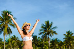 Blissful woman enjoying tropical caribbean vacation freedom. Happy blissful woman in white bikini enjoying tropical beach and caribbean summer vacation. Tanned Stock Photos