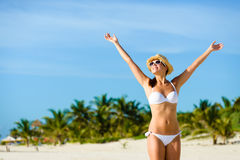 Blissful woman enjoying tropical vacation freedom and happiness. Beautiful blissful woman in bikini enjoying tropical beach and caribbean summer vacation. Tanned Stock Images