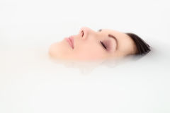 Blissful woman soaking in a hot bath. Blissful beautiful young woman pampering herself soaking in a hot bath with just her face visible above the soapy water as Royalty Free Stock Image