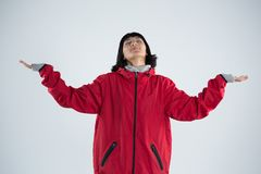 Blissful woman standing with arms outstretched. Against white background Stock Images