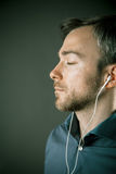 Blissful young man listening to music. On a set of ear plugs standing with his eyes closed in contentment, close up profile view on grey Royalty Free Stock Images