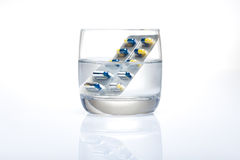 Blister of blue and yellow pills in a glass of water Stock Photos