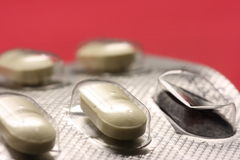 Blister with pills. Detail of blister with pills on red background Stock Photo