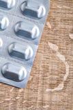 Blisterpackung mit medizinischen Pillen auf hölzernem Brett Stockfotografie