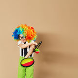 Blithesome children. Portrait of happy clown boy wearing large n. Eon coloured wig. Kid in clown wig and eyeglasses playing catch ball game Stock Photo
