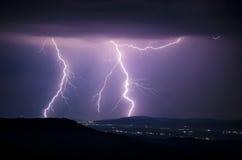 Blitz über den Lichtern eines Dorfs in der Nacht Lizenzfreie Stockfotos
