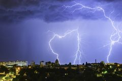 Blitz über der Stadt im nächtlichen Himmel schlägt das Dach des Hauses Stockfotografie
