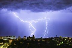 Blitz über der Stadt im nächtlichen Himmel schlägt das Dach des Hauses Lizenzfreies Stockfoto