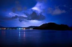 Blitz über ruhigem See und einem Berg Stockfoto