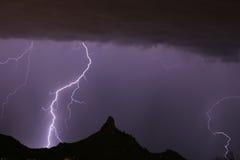 Blitz, der an der Berggipfel-Spitze schlägt Stockfotografie