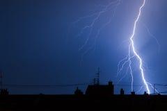 Blitz, der Gebäudedachspitzen im Gewitter schlägt Stockfotografie