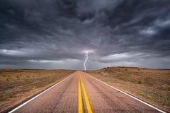 Blitz, der nahe bei einer Landstraße schlägt Stockbilder