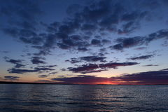 Blitz eines hellen roten Sonnenuntergangs auf dem Horizont im Himmel über dem See Stockbilder