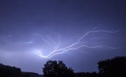 Blitz im Himmel auf dem Hintergrund von Bäumen Lizenzfreie Stockfotografie