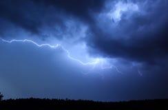 Blitz im Himmel auf dem Hintergrund von Bäumen Stockfotografie