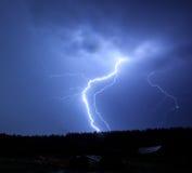 Blitz im Himmel auf dem Hintergrund von Bäumen Lizenzfreie Stockfotos