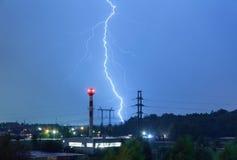 Blitz im nächtlichen Himmel über dem Kesselhaus und den Stromleitungen Lizenzfreie Stockfotografie