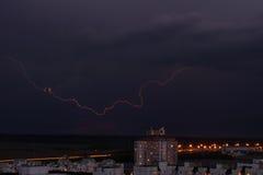 Blitz im nächtlichen Himmel über den Stadthäusern Stockfoto