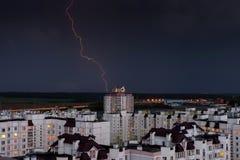 Blitz im nächtlichen Himmel über den Stadthäusern Stockbild