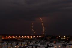 Blitz im nächtlichen Himmel über den Stadthäusern Lizenzfreies Stockfoto