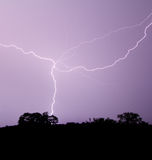Blitz kreuzt purpurroten Himmel Stockbild