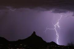 Blitz-Schraube, die neben Berggipfel-Spitze schlägt Stockfotos