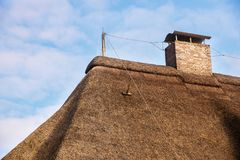 Blitzableiter auf einem Strohdach mit einem Kamin gegen ein blaues s Stockfotografie