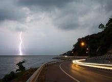 Blitzblitz im Meer in der Dämmerung mit Beleuchtung von den Autos Lizenzfreies Stockfoto
