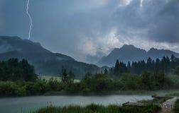 Blitzbolzen, der einen Hügel über See schlägt Lizenzfreie Stockbilder