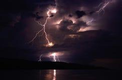 Blitze an der Küste, die auf Insel mit schlägt Lizenzfreie Stockfotos