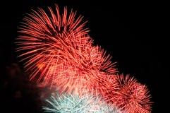 Blitze des rosa und weißen Feiertagsfeuerwerks gegen den schwarzen Himmel Lizenzfreies Stockbild