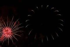 Blitze des weißen und rosa Feiertagsfeuerwerks gegen den schwarzen Himmel Stockfotografie