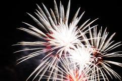 Blitze des weißen und roten Feiertagsfeuerwerks gegen den schwarzen Himmel Lizenzfreies Stockbild