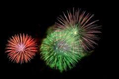 Blitze von Feuerwerken der grünen, roten und purpurroten Farbe Lizenzfreie Stockfotografie