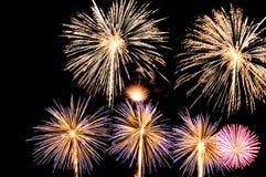 Blitze von Feuerwerken von weißen, gelben, rosa und blauen Farben Stockfotografie